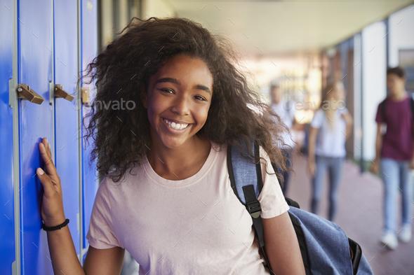 Portrait of black teenage girl by lockers in school corridor - Stock Photo - Images