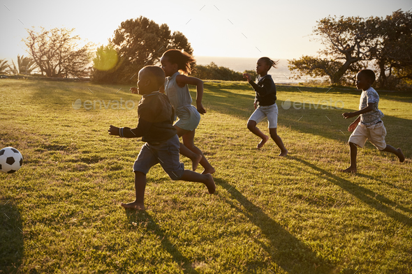 Four elementary school kids playing football in a field - Stock Photo - Images