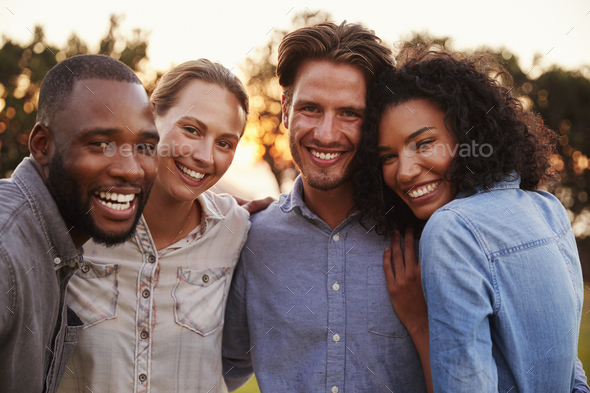 Portrait of two happy young couples smiling and embracing - Stock Photo - Images