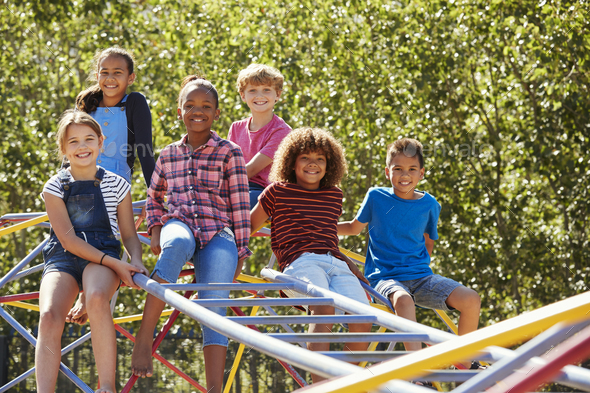 Pre-teen friends sitting on climbing frame in playground - Stock Photo - Images