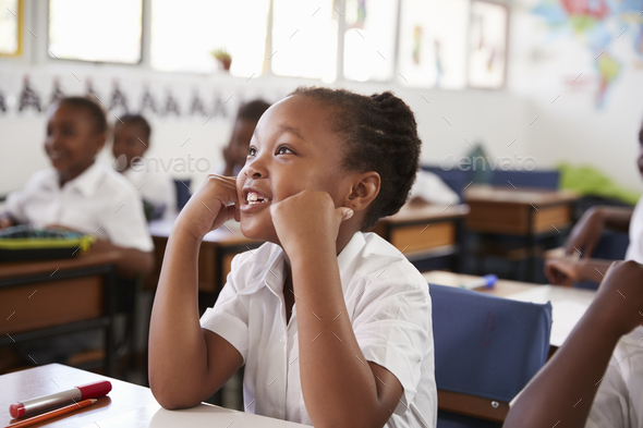 Girl listening during a lesson at an elementary school - Stock Photo - Images