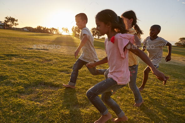 Four children running barefoot in a park - Stock Photo - Images