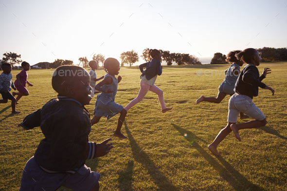 Elementary school boys and girls running in an open field - Stock Photo - Images