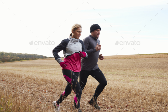 Mature Couple Running Around Autumn Field Together - Stock Photo - Images