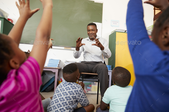Elementary school kids sitting on floor listening a teacher - Stock Photo - Images