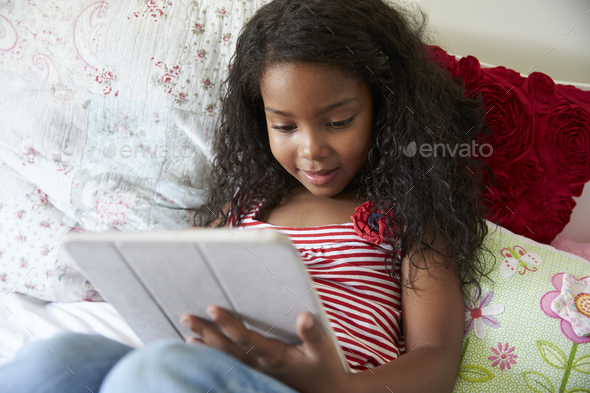 Young Girl Lying On Bed Using Digital Tablet - Stock Photo - Images