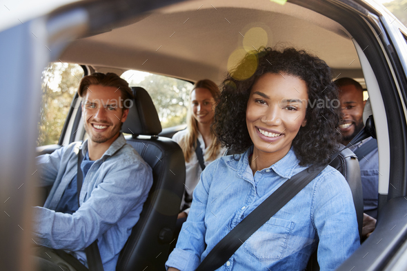 Four adult friends in a car on a road trip smiling to camera - Stock Photo - Images