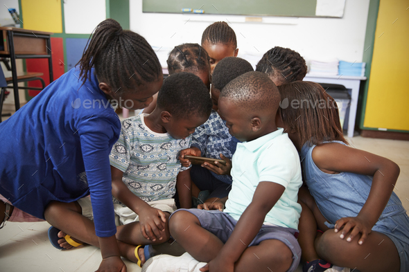 Elementary school kids sitting on floor looking at a book - Stock Photo - Images
