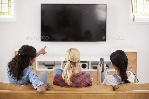 Rear View Of Female Friends Sitting On Sofa Watching Television - Stock Photo - Images