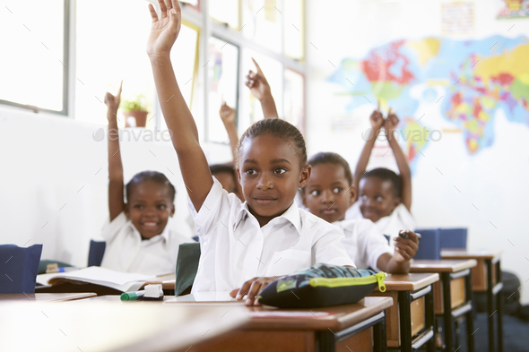Kids raising hands during a lesson at an elementary school - Stock Photo - Images