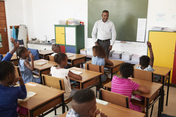 Teacher and kids during a lesson at an elementary school - Stock Photo - Images