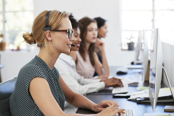 Woman with headset at computer in office beside colleagues - Stock Photo - Images