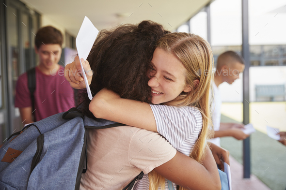 Two girls celebrating exam results in school corridor - Stock Photo - Images