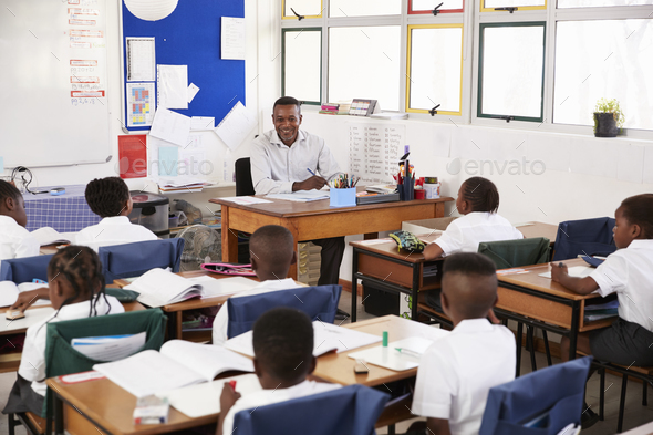 Teacher and kids sitting at desks in elementary classroom - Stock Photo - Images