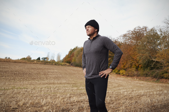 Mature Male Runner Pausing For Breath During Exercise In Woods - Stock Photo - Images