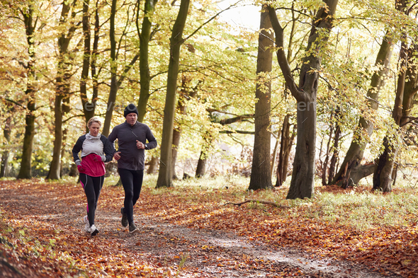 Mature Couple Running Through Autumn Woodland Together - Stock Photo - Images