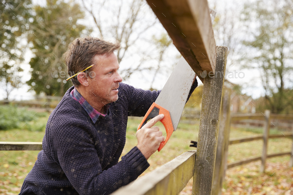 Mature Man Fixing Outdoor Fence With Saw - Stock Photo - Images