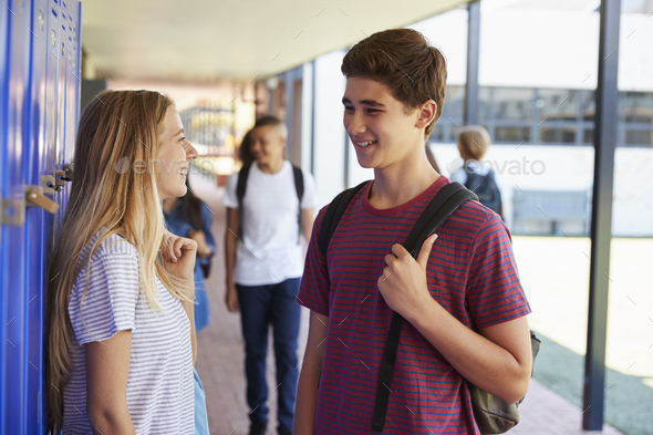 Two friends talking in school corridor at break time - Stock Photo - Images