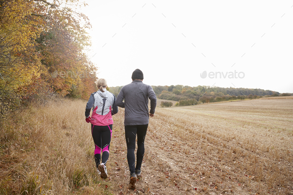 Rear View Of Mature Couple Running Around Autumn Field - Stock Photo - Images