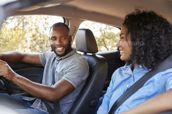 Young black couple in a car looking at each other smiling - Stock Photo - Images