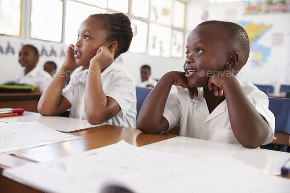 Two kids listening during a lesson at an elementary school - Stock Photo - Images