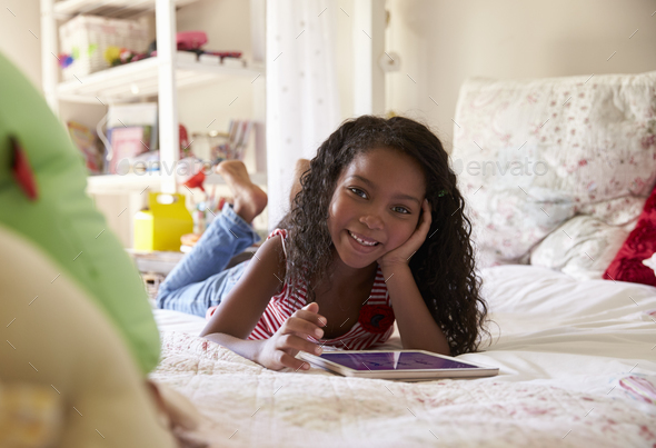 Portrait Of Young Girl Lying On Bed Using Digital Tablet - Stock Photo - Images