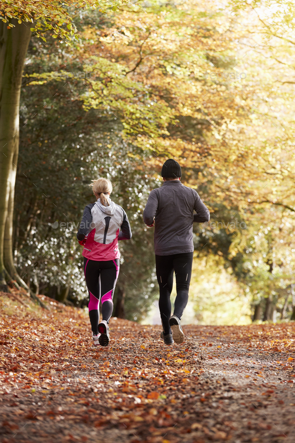 Rear View Of Mature Couple Running Through Autumn Woodland - Stock Photo - Images
