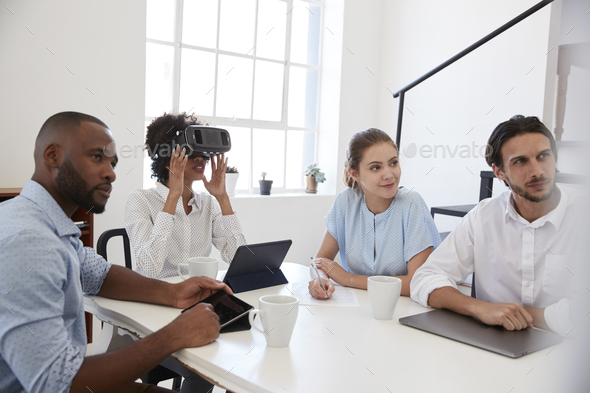 Woman in VR goggles at a desk with colleagues in an office - Stock Photo - Images