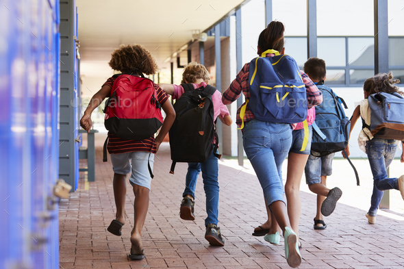 School kids running in elementary school hallway, back view - Stock Photo - Images