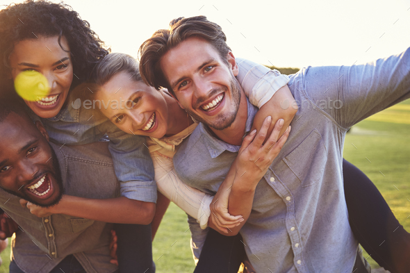 Two laughing couples piggybacking outdoors, close up - Stock Photo - Images
