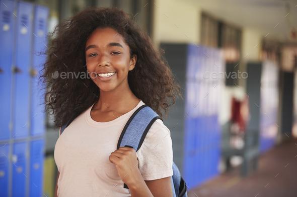 Happy black teenage girl smiling in high school corridor - Stock Photo - Images