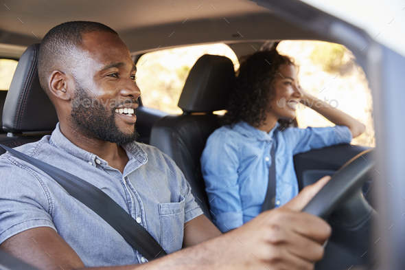 Young black couple in car on a road trip look ahead smiling - Stock Photo - Images