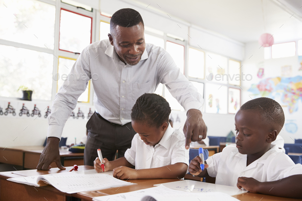 Teacher stands helping elementary school kids at their desks - Stock Photo - Images