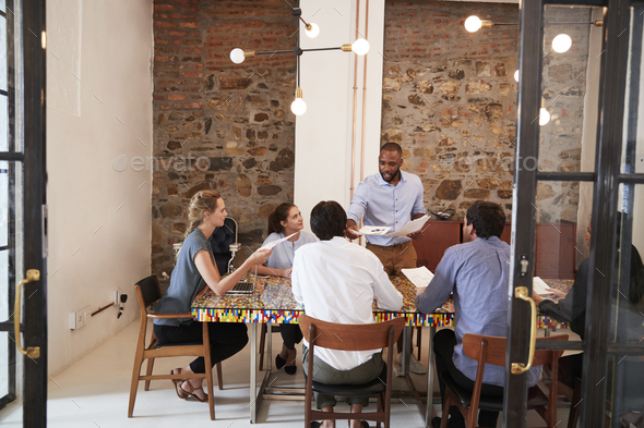 Young black man handing out paperwork at a team meeting - Stock Photo - Images