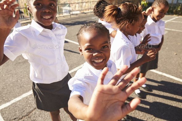 Young African schoolgirls in a playground waving to camera - Stock Photo - Images