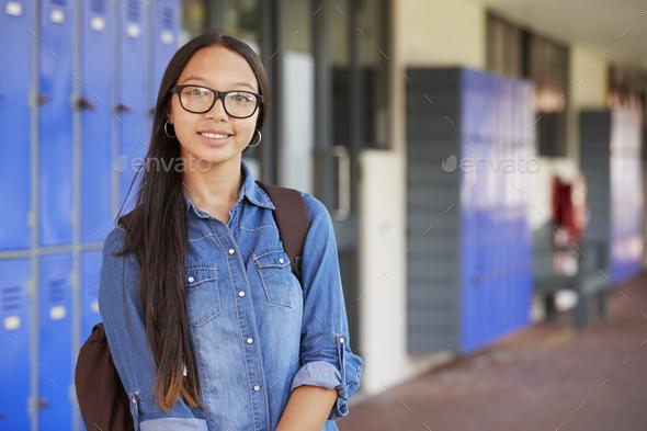 Happy Asian teenage girl smiling in high school corridor - Stock Photo - Images