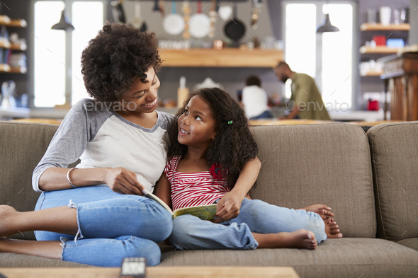 Mother And Daughter Sit On Sofa In Lounge Reading Book Together - Stock Photo - Images