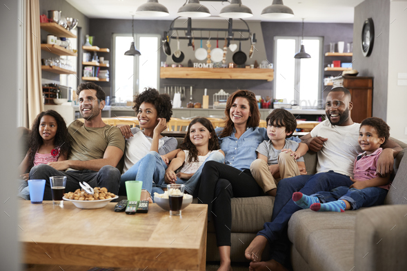 Two Families Sitting On Sofa Watching Television Together - Stock Photo - Images