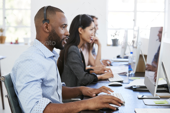 Young black man with headset working at computer in office - Stock Photo - Images
