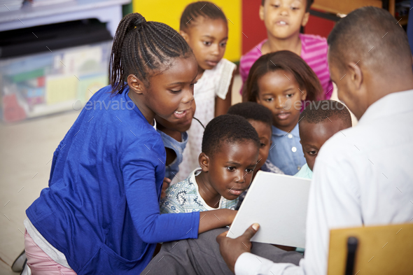 Teacher showing kids a book during elementary school lesson - Stock Photo - Images