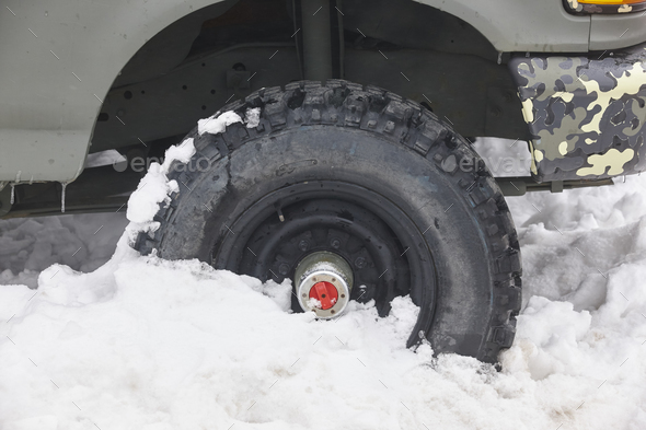 Four wheel vehicle tyre trapped on the snow. Winter time - Stock Photo - Images