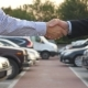 Two Businessmen Shaking Hands of Each Other with Cars in Parking at Background. - VideoHive Item for Sale