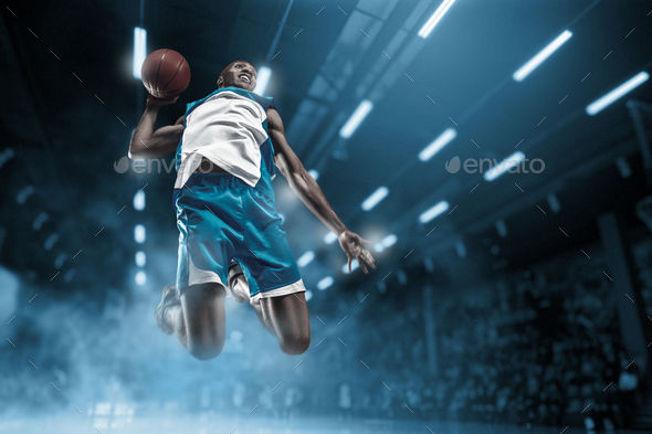 Basketball player on big professional arena during the game. Basketball player making slam dunk. - Stock Photo - Images