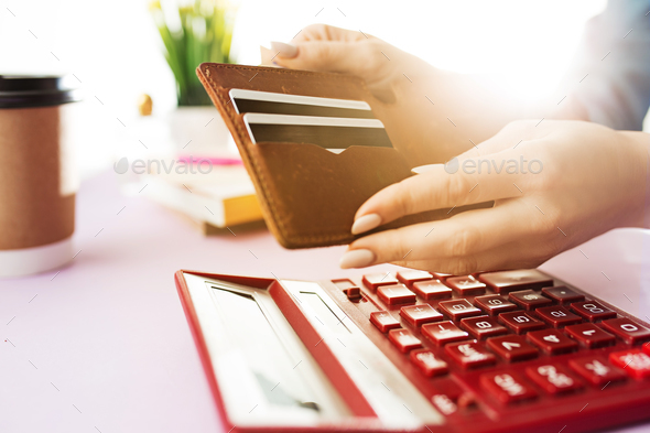 woman is holding purse, credit card in hands and calculating the costs - Stock Photo - Images