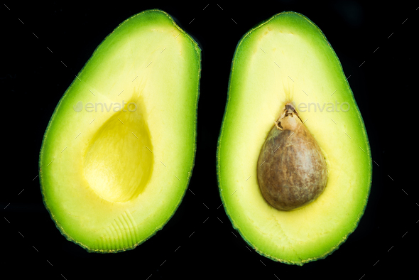 Avocado halves on dark background,flat lay - Stock Photo - Images