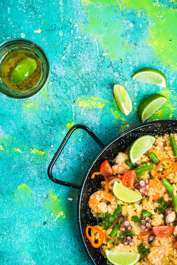 Seafood paella in pan served with beer and lime - Stock Photo - Images