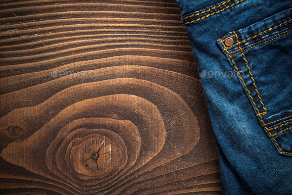Blue denim jeans on wooden background - Stock Photo - Images