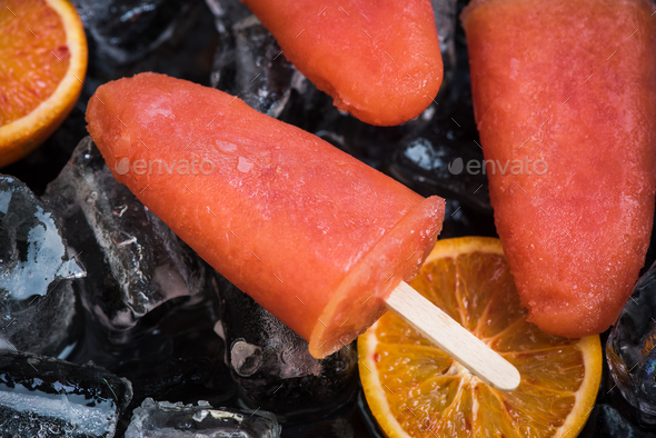 Orange juice popsicles over ice - Stock Photo - Images