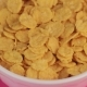 Yellow Breakfast Cornflakes in a White Bowl on Pink Background. - VideoHive Item for Sale