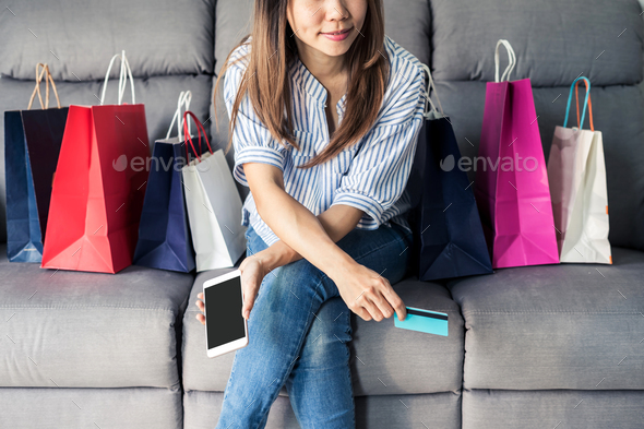 Happy asian woman holding credit card and smart phone - Stock Photo - Images